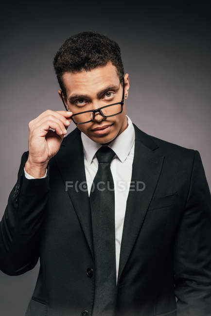 Handsome african american businessman in glasses and suit on dark background — Stock Photo