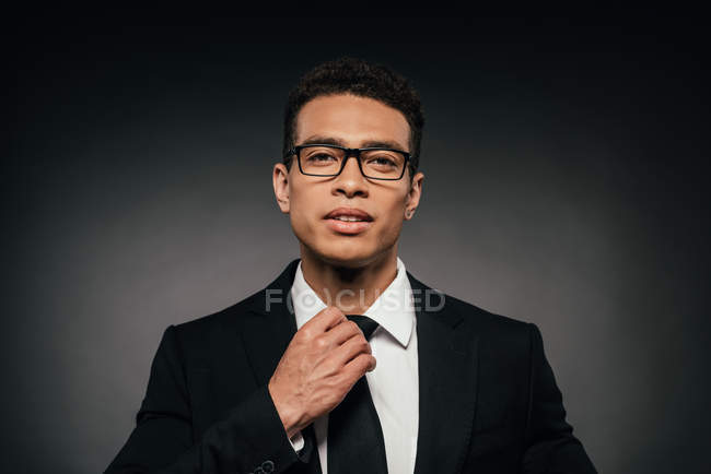 Handsome african american businessman in glasses and suit touching tie on dark background — Stock Photo