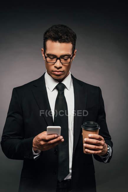 Beau homme d'affaires américain africain dans des glaces et le costume retenant le café pour aller et utilisant le smartphone sur le fond foncé — Photo de stock