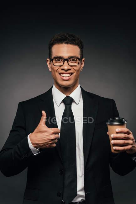 Beau homme d'affaires américain africain de sourire dans des glaces et le costume retenant le café pour aller et affichant le pouce vers le haut sur le fond foncé — Photo de stock
