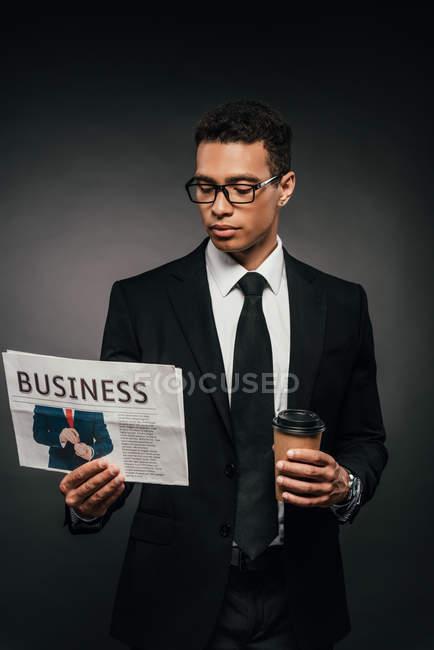 Beau homme d'affaires américain africain dans des glaces et le costume retenant le café pour aller et lire le journal sur le fond foncé — Photo de stock