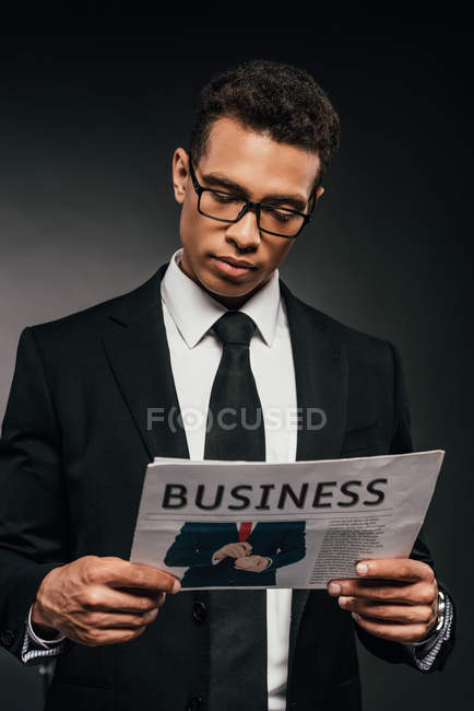 Handsome african american businessman in glasses and suit reading business newspaper on dark background — Stock Photo