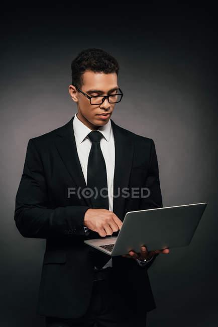 Homme d'affaires américain africain utilisant l'ordinateur portatif sur le fond foncé — Photo de stock