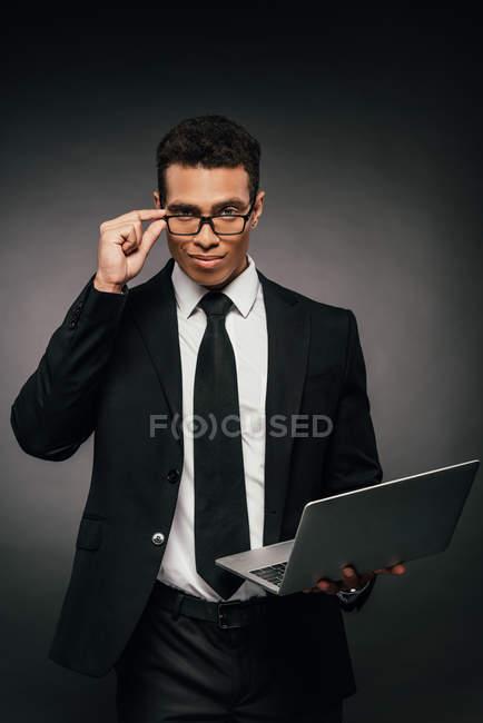 Beau homme d'affaires américain africain dans des glaces et l'ordinateur portatif de fixation de costume sur le fond foncé — Photo de stock