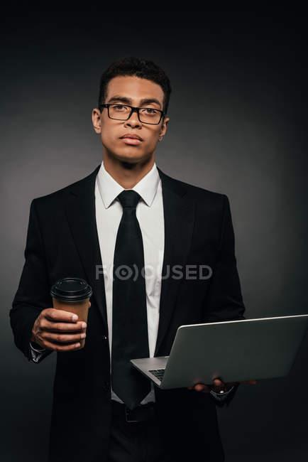 Homme d'affaires américain africain retenant l'ordinateur portatif et la tasse de papier sur le fond foncé — Photo de stock