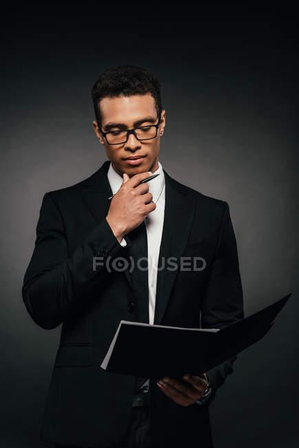Homme d'affaires américain africain réfléchi lisant des documents sur le fond foncé — Photo de stock