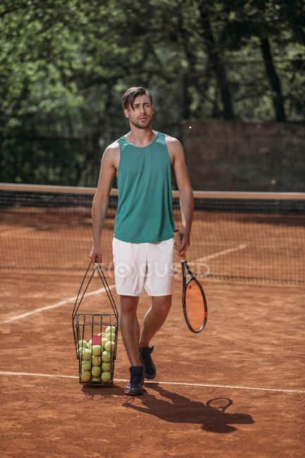 Tenista con cesta de pelotas en cancha - foto de stock