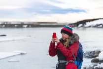 Woman taking photo with mobile phone, Iceland, Europe — Stock Photo