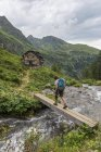 Hiker crossing wooden bridge over mountain river, Golling Hut, Rohrmoos-Untertal, Schladming Tauern, Styria, Austria, Europe — Stock Photo