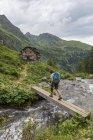 Hiker crossing wooden bridge over mountain river, Golling Hut, Rohrmoos-Untertal, Schladming Tauern, Styria, Austria, Europe — Stock Photo