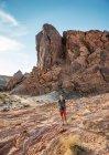 Чоловік, що стоїть на формування Червона скеля у вечірній світло, пустелі Мохаве, штат Невада, США — стокове фото