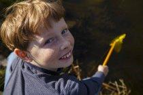 Vista de alto ângulo de menino de ruiva pescando no lago com net — Fotografia de Stock