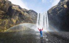Randonneur en face de la cascade de Skogafoss — Photo de stock