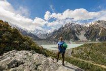 Hiker standing on rocks — Stock Photo