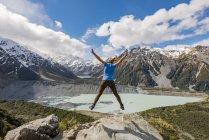Hiker makes air jump — Stock Photo