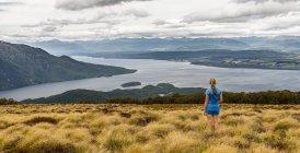 Female hiker looking at lake Te Anau and Southfiord — Stock Photo