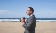 Businessman with binoculars at beach — Stock Photo