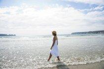 Woman walking through small waves — Stock Photo