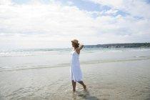 Жінка вигулює через маленькими хвилями — стокове фото