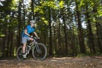 Ciclista na bicicleta de montanha andando pela floresta — Fotografia de Stock