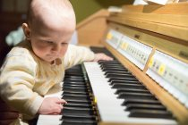 Girl playing on home piano — Stock Photo