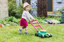 Girl with toy lawn mower — Stock Photo