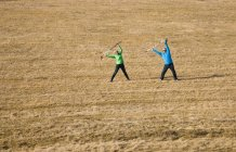 Senio couple with walking poles stretching in field — Stock Photo