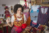 Button maker in colorful dirndl — Stock Photo