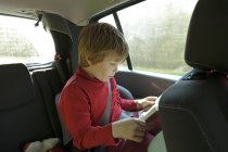 Boy reading in car — Stock Photo