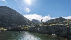 Hiker by a mountain lake — Stock Photo