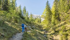 Backpackers walking on trail in mountains — Stock Photo