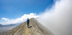 Rear view of man on narrow path on the way to crater of smoking volcano Gunung Bromo in National Park Bromo-Tengger-Semeru, Java, Indonesia. — Stock Photo