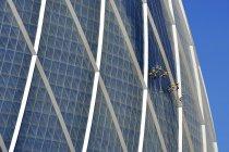 Limpiacristales en raíces moneda edificio, Abu Dhabi, Emiratos Árabes Unidos, Asia - foto de stock