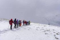 Hiking group ascending during snowfall in Ramingstein, Salzburg, Austria, Europe — Stock Photo