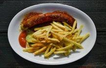 Curry salsiccia con patate fritte sulla piastra, close-up — Foto stock