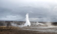 People watching eruption of Geyser Strokkur at Haukadalur Geothermal Field, Iceland — Stock Photo
