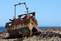 Rusty wreck of fish trawler on rocky shore, Camarones, Chubut, Argentina, South America — Stock Photo