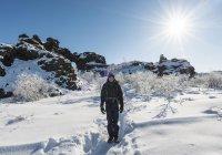 Junger Mann auf Wanderweg in verschneiter Landschaft der Krafla, Dimmuborgir Nationalpark, Myvatn, Island, Europa — Stockfoto