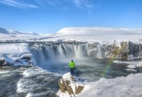Rear view of man standing in front of waterfall Godafoss, Iceland, Europe — Stock Photo
