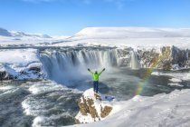 Man standing with arms outstretched in front of waterfall Godafoss with rainbow, Iceland, Europe — Stock Photo