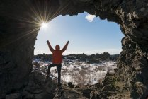 Man with arms outstretched in rock arch with volcanic landscape of Krafla, Dimmuborgir National Park, Myvatn, Iceland, Europe — Stock Photo