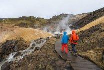 Чоловічий туристів, прогулянки на пару Піші прогулянки trail геотермальних районі Seltun, Національний заповідник Reykjanesfolkvangur, Ісландія, Європа — стокове фото