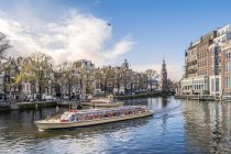 Panorama of Amsterdam with Mint tower and touristic boat, Netherlands, Europe. — Stock Photo