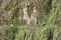 Car riding on narrow Yungas mountain road between La Paz and Coroico, Bolivia, South America — стоковое фото