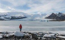Чоловік, що стоїть на заморожені Fjallsarlon льодовика лагуни, Ісландія, Європа — стокове фото