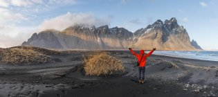 Man in red jacket with arms outstretched on lava beach in mountain range Klifatindur, Austurland, Iceland, Europe — Stock Photo