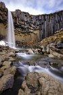 Svartifoss Black Falls waterfall and river Storilaekur with basalt pillars, Skaftafell National Park, Suourland, Southern Region, Iceland, Europe — Stock Photo