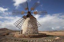 Ветряная мельница в бесплодном ландшафте Молино-де-Тефия, Тефия, Фуэртевентура, Канарские острова, Испания, Европа — стоковое фото