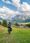 Young female cyclist on cycle path Via Claudia Augusta crossing the Alps near Ehrwald, Tyrol, Austria, Europe — Stock Photo
