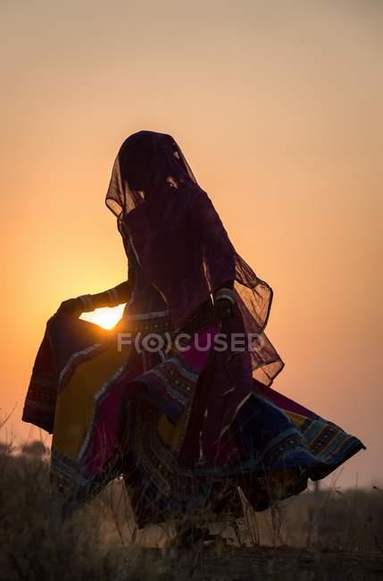 Mulher dançando na frente do sol — Fotografia de Stock